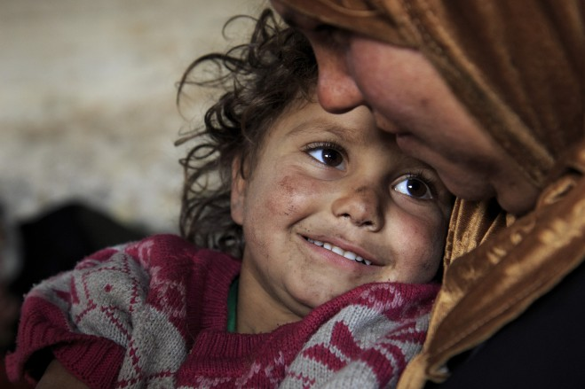 Fatima*, 3, sits on her motherâs lap inside their familyâs temporary shelter in the suburbs of Idleb where they have been living for few months after they were forced to leave their hometown because of the violent clashes and heavy bombardment